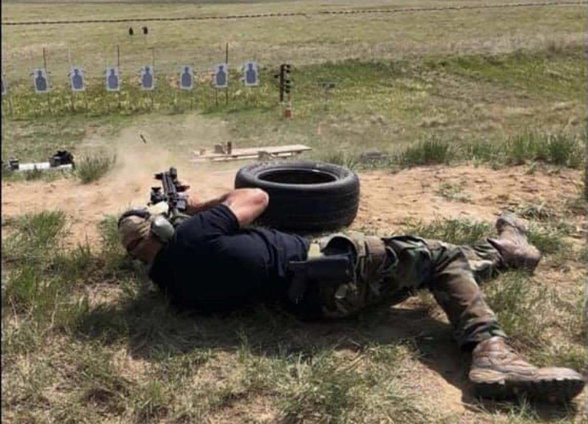 Man shooting carbine on ground